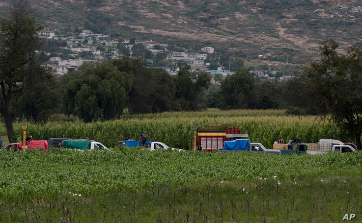 FILE -  Gasoline thieves wait in line to steal gas from an illegal tap into a state-owned pipeline, in the middle of a cornfield in San Bartolome Hueyapan, Tepeaca, Mexico, July 11, 2017.