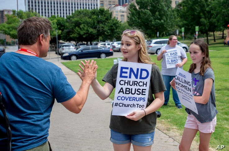 FILE - Claire Summers, 16, gets a high five as she and her sister Ella Summers, 10, right, protest the Southern Baptist Convention's treatment of women outside the convention's annual meeting at the Kay Bailey Hutchison Convention Center in Dallas, J...