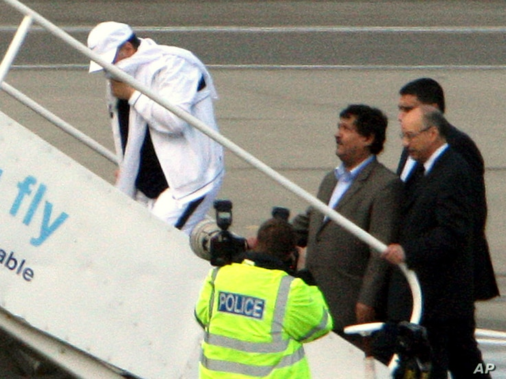 FILE - Lockerbie airline bomber Abdel Basset al-Megrahi, left, who was released from prison on compassionate grounds because he was terminally ill, boards an airplane accompanied by Libyan officials at Glasgow airport, Glasgow, Scotland, Aug. 20, 200