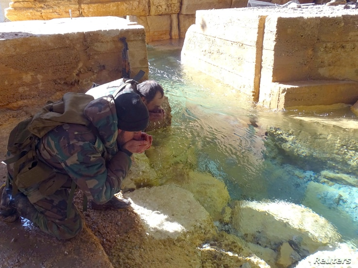 Syrian government soldiers drink from a water pumping station in the village of Ain al-Fija in the Wadi Barada valley near Damascus.