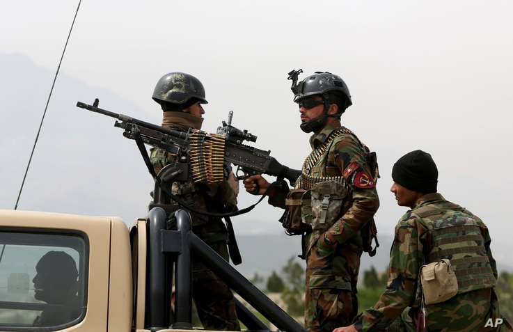FILE - Afghan military soldiers stand stand alert at the entrance gate of the new parliament building after a rocket attack in Kabul, Afghanistan.