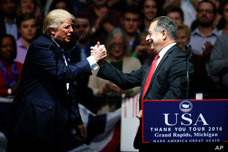 President-elect Donald Trump thanks Dow Chemical Company Chairman and Chief Executive Officer Andrew Liveris during a rally, in Grand Rapids, Mich., Dec. 9, 2016.