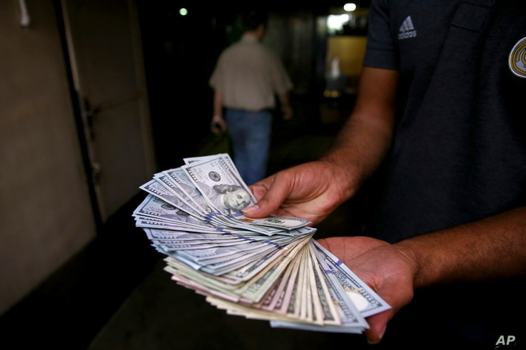 An illegal street money exchanger poses with his U.S. banknotes in downtown Tehran, Iran,  Aug. 7, 2018. Money exchange shops across Iran cautiously reopened after being shut for five months.
