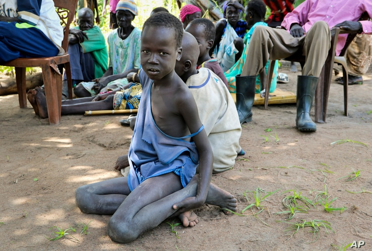 In this photo taken Friday, Aug. 17, 2018, a young boy sits on the ground watching an aid distribution by Oxfam on the island of Nyajam, off the mainland from the opposition-held town of Nyal in Unity state, in South Sudan.