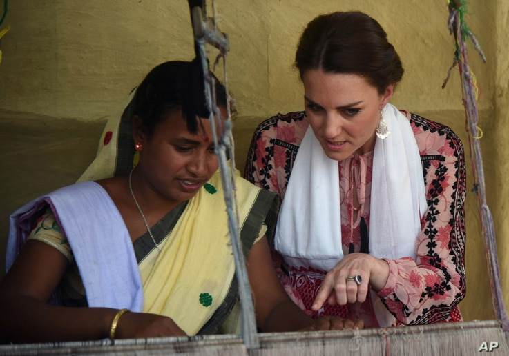 FILE - Britain's Duchess of Cambridge, right, watches an Indian woman make hand woven cloth in Panbari village, east of Gauhati, northeastern Assam state, India, April 13, 2016.