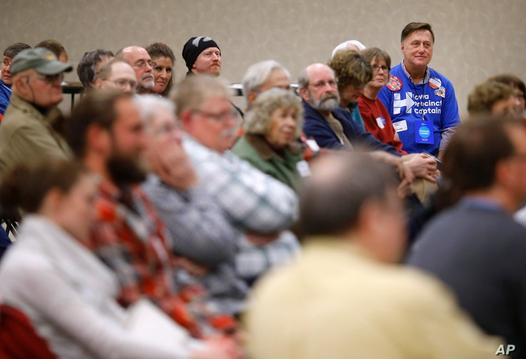 John Grause, top right, precinct captain for Democratic presidential candidate Hillary Clinton, sits with voters during a Democratic party caucus in Nevada, Iowa, Feb. 1, 2016.