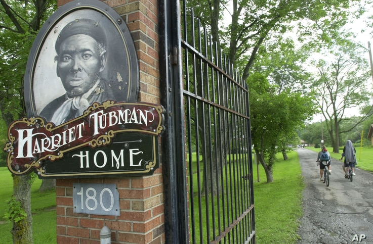 FILE - Children ride their bikes down the drive passing the Harriet Tubman Home in Auburn, N.Y. The home of the abolitionist is along a trail of memorials and museums from New England south to Washington, D.C., that extol women's achievements in mold