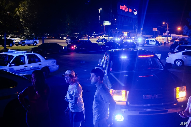 Bystanders look on as emergency personnel respond to the scene of a deadly shooting at the Grand Theatre in Lafayette, La., Thursday, July 23, 2015.