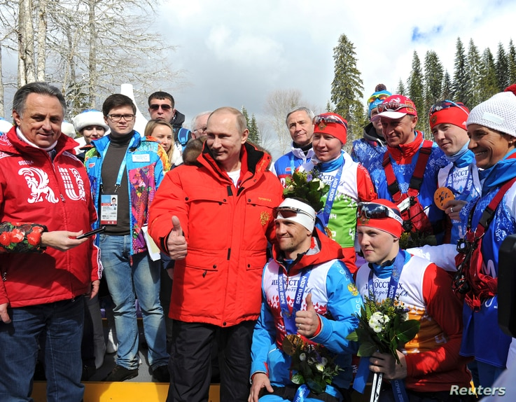 File - Russian President Vladimir Putin (C) poses for a picture with Russian athletes who won the cross-country skiing open relay at the 2014 Sochi Winter Paralympic Games, March 15, 2014.