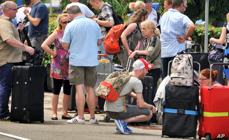 British tourists queue with their luggage to leave by charter flight from the international airport in Mombasa, Kenya Friday, May 16, 2014.