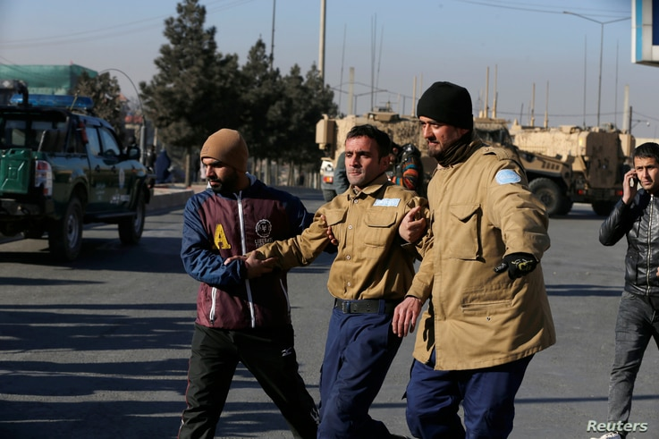 A wounded security guard receives help after being rescued from Kabul's Intercontinental Hotel during an attack by gunmen in Kabul, Afghanistan, Jan. 21, 2018.