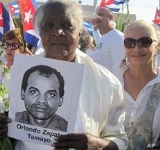 Woman holds a picture of Orlando Zapata Tamayo, who died in February after an 85-day hunger strike, at a rally in LIttle Havana, Miami, 25 March 2010