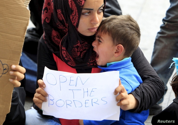 A migrant holds a sign in front of Keleti railway station in Budapest, Hungary, Sept. 4, 2015.