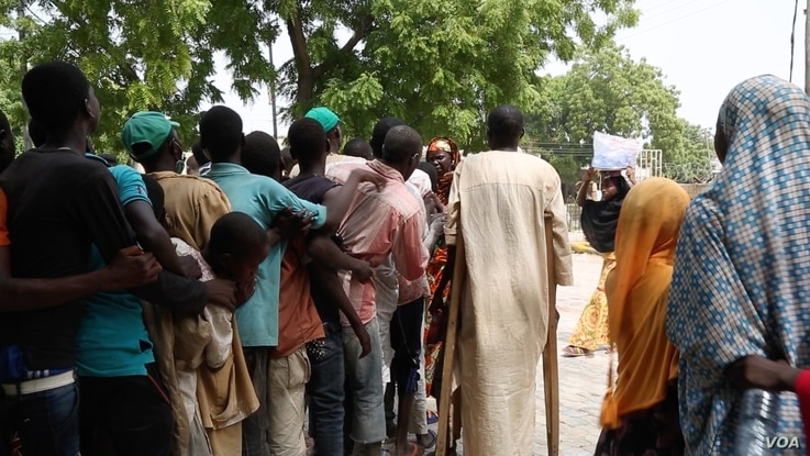 People line up along a sidewalk in front of Hajia Hawa as she passes out vouchers for free food,Maiduguri, Nigeria, Sept. 2016. (Photo: C. Oduah)