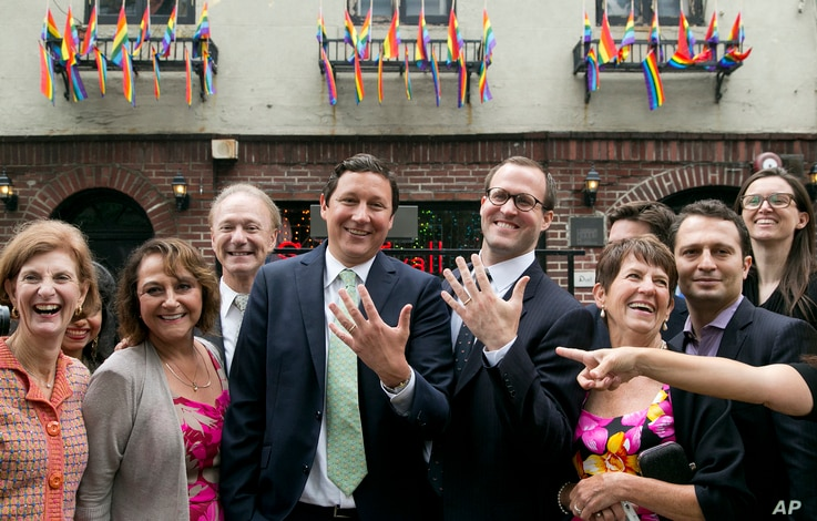 David Turley, center left, and his husband Peter Thiede, display their wedding bands while posing for photos with friends and family, Sunday, June 28, 2015 in front of New York's Stonewall Inn. New York Gov. Andrew Cuomo earlier wed the New York City...