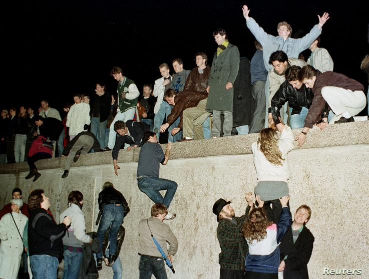 FILE - East German citizens climb the Berlin wall at the Brandenburg Gate as they celebrate the opening of the East German border.