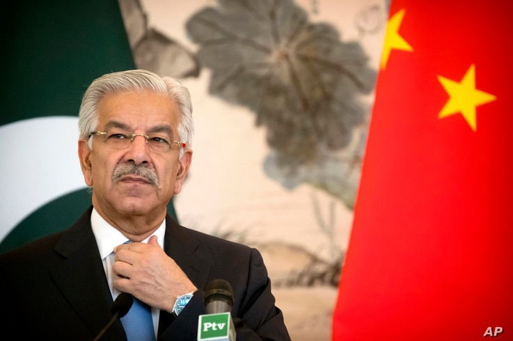 Pakistan's Foreign Minister Khawaja Muhammad Asif adjusts his necktie during a joint press conference at the Diaoyutai State Guesthouse in Beijing, Sept. 8, 2017.
