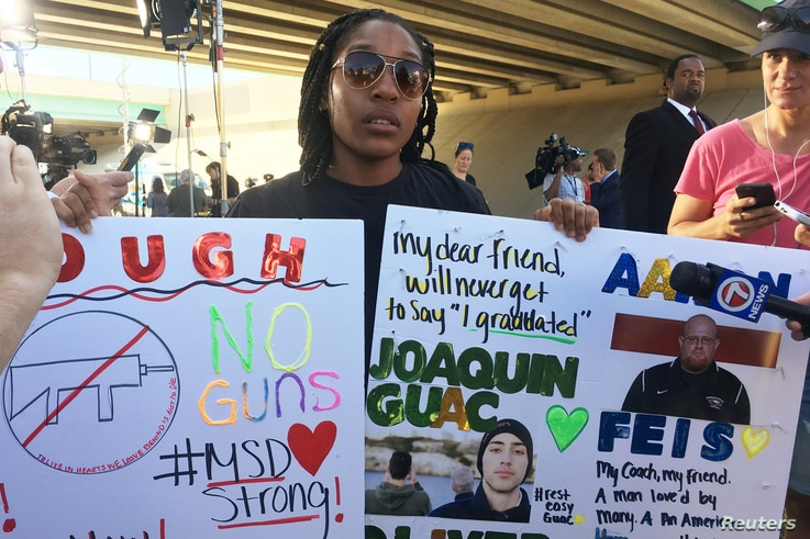 Tyra Hemans, a 19-year-old senior at Marjory Stoneman Douglas High School, sobs as she holds signs honoring slain teachers and friends near the police cordon around the school in Parkland Florida, Feb. 15, 2018.