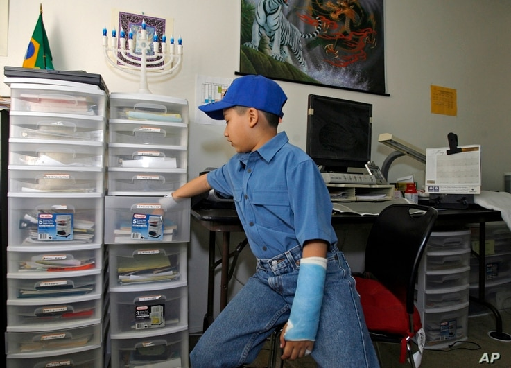Moshe Kai Cavalin, 10, keeps his college classes assignments organized in separate clear plastic drawers at his home studio in Downey, Calif.
