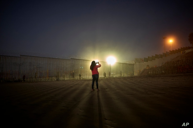 A woman takes a picture as floodlights from the U.S. side light up a border fence, topped with razor wire, Jan. 10, 2019, along the beach in Tijuana, Mexico.