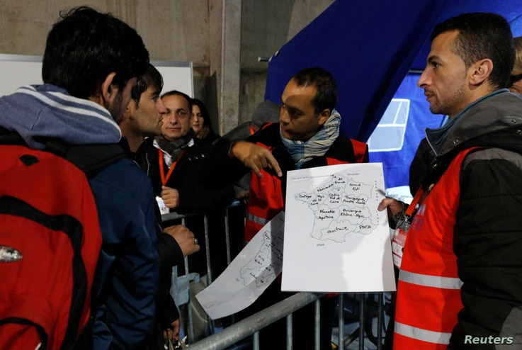 "Migrants look at a map of France at a processing center to be registered on the second day of their evacuation and transfer to reception centers in France, during the dismantlement of the camp called ""the jungle"" in Calais, France, Oct. 25, 2016."