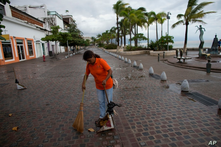 A city cleaner sweeps normal leaves and debris from a seafront walkway, the morning after Hurricane Patricia passed further south sparing Puerto Vallarta, Mexico, Oct. 24, 2015.