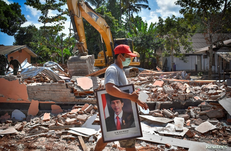 A man carries a framed picture of Indonesian President Joko Widodo from a school damaged by an earthquake in Gunungsari, Lombok, Indonesia, Aug. 12, 2018.
