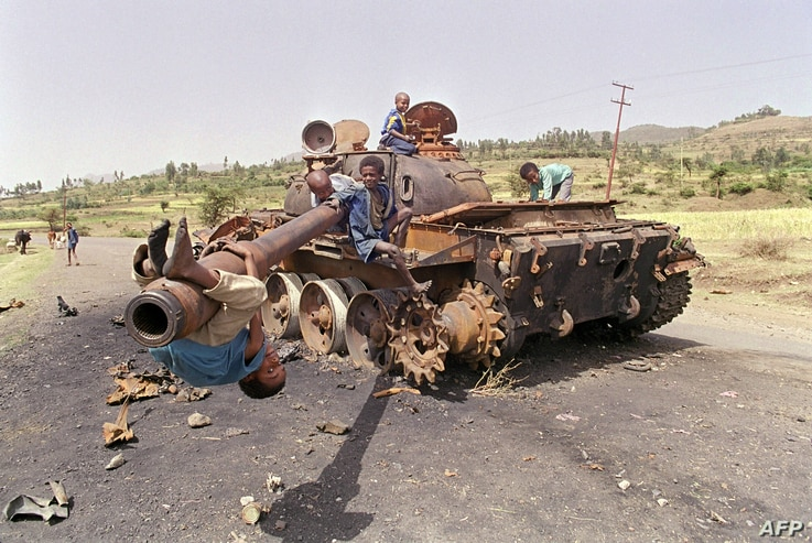 FILE - Eritrean children play on an Ethiopian army tank, June 7, 1991. The tank was destroyed by Eritrean Liberation Front (EPLF) rebels in the battle for Amara, capital of Eritrea, that fell days earlier to EPLF rebels after 17 years of war.