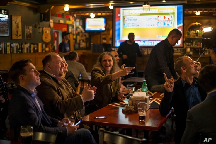 FILE - Russian political experts react as they watch a live telecast of the U.S. presidential election in the Union Jack pub in Moscow, Russia, Nov. 9, 2016.