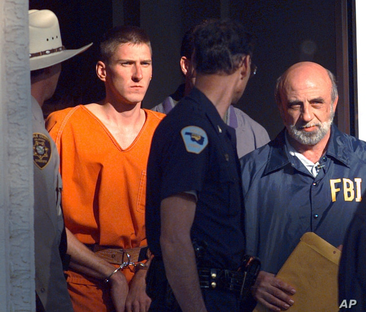 FILE - In this April 21, 1995 file photo, Timothy James McVeigh is lead out of the Noble County Courthouse by state and federal law enforcement officials in Perry, Okla., after being identified as a suspect in the bombing of the Oklahoma City Federal...