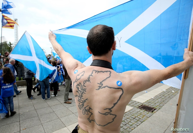 "A ""Yes"" supporter with a tattoo of Scotland on his back holds a Saltire flag at a rally outside the BBC in Glasgow, Scotland, Sept. 14, 2014."