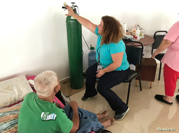 Dr. Lourdes Marrero shows a patient how to use an oxygen tank if the generator fails at a public shelter in Orocovis, Puerto Rico, Oct. 3, 2017.