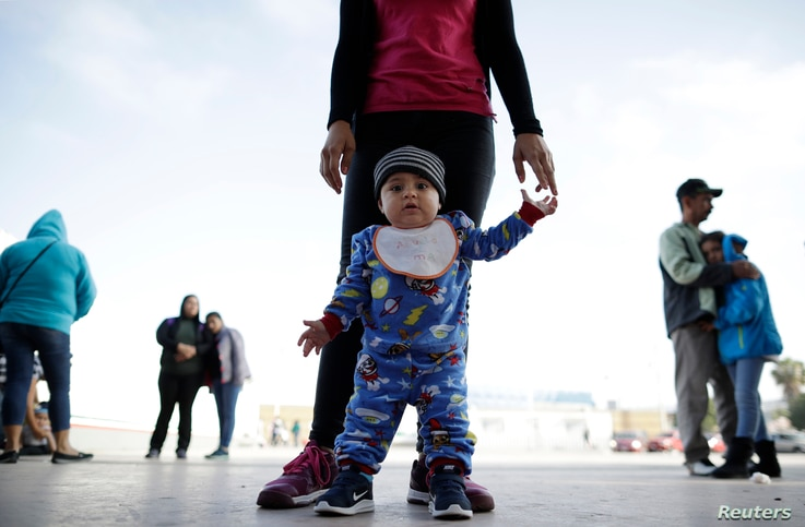 Nine month-old Jesus Alberto Lopez, center, stands with his mother, Perla Murillo, as they wait with other families to request political asylum in the United States, across the border in Tijuana, Mexico.