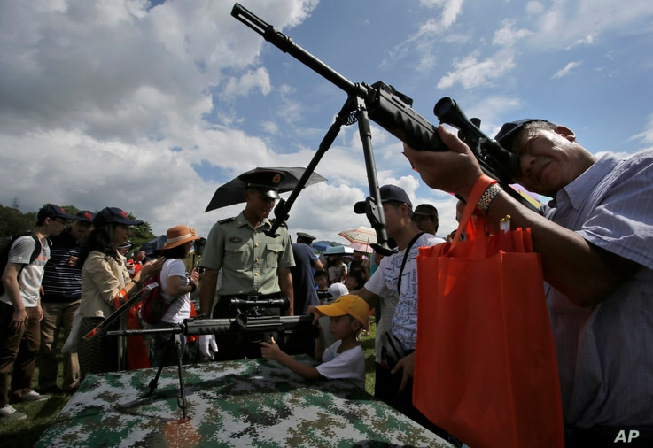 Visitors take aim with rifles at a military base during an open day event of the Chinese People's Liberation Army (PLA) in Hong Kong,  June 29, 2014.