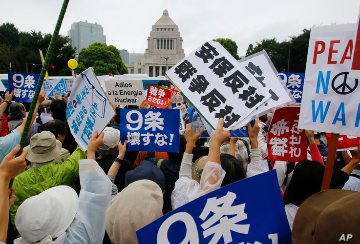 FILE - In this Aug. 30, 2015 file photo, protesters hold anti-war placards in front of the National Diet building during a rally in Tokyo.  Japan holds an election on July 10, 2016, for the upper house of parliament that could affect the country's ...