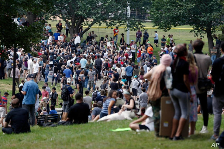 """People assemble on Boston Common before a planned """"Free Speech"""" rally by conservative organizers begins, Aug. 19, 2017, in Boston."""