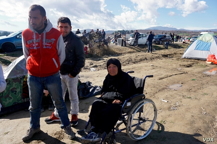 A wheelchair-bound migrant woman waits in a makeshift refugee camp in the northern Greek border town of Idomeni, seeking passage to another European destination, March 4, 2016.