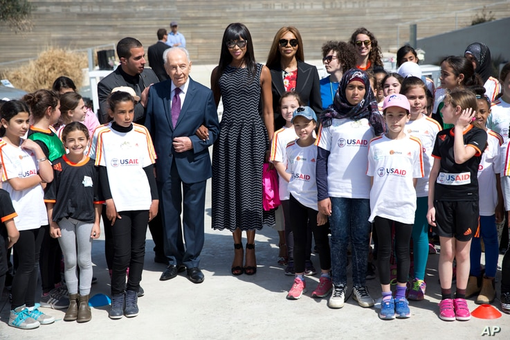 Naomi Campbell, center, meets with former Israeli President Shimon Peres, including Israeli and Palestinian girls, during an event for International Women's Day in Tel Aviv, Israel, March 8, 2016.