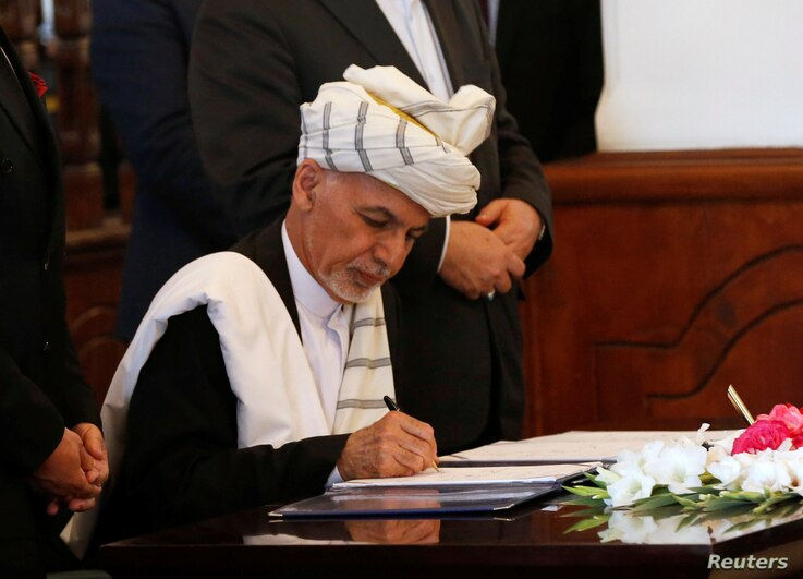 FILE - Afghan President Ashraf Ghani signs a peace agreement with Hizb-i-Islami, led by Gulbuddin Hekmatyar, in Kabul, Afghanistan, Sept. 29, 2016.