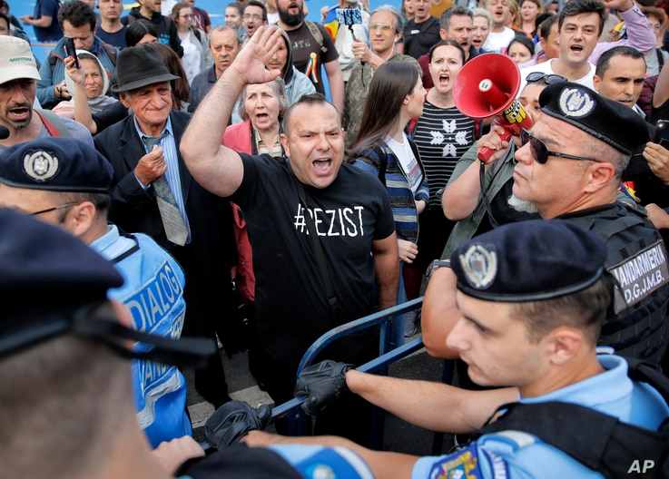 A protester shouts at riot police setting up fences during a protest outside the government headquarters in Bucharest, Romania, May 12, 2018.