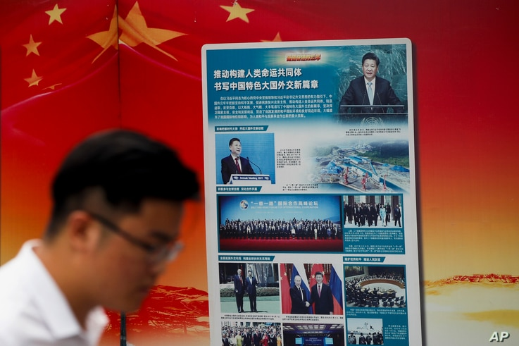 "A man walks by a government propaganda billboard promoting Chinese President Xi Jinping's signature ""One Belt One Road"" outside a subway station in Beijing, Aug. 28, 2018."
