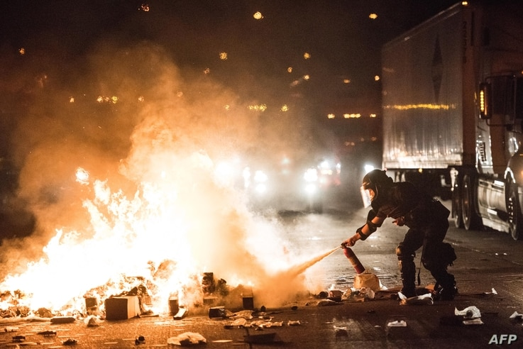 A police officer attempts to extinguish a fire on the I-85 (Interstate 85) during protests following the death of a man shot by a police officer on Sept. 21, 2016 in Charlotte, NC.