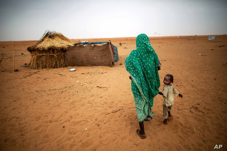 File photo released by the United Nations African Union Mission in Darfur (UNAMID), a woman holds hands with her daughter as they walk at the Zam Zam refugee camp for internally displaced people (IDP) in North Darfur, Sudan.