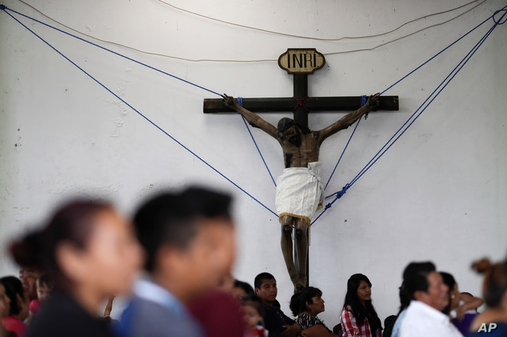A crucifix, recovered from a collapsed church, is held up by ropes inside an auditorium during a Mass, in Tepeojuma, Mexico, Sept. 24, 2017.