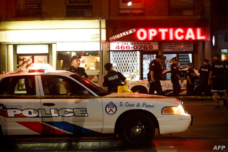 Police officers walk the scene at Danforth St. at the scene of a shooting incident, in Toronto, Canada, July 22, 2018.