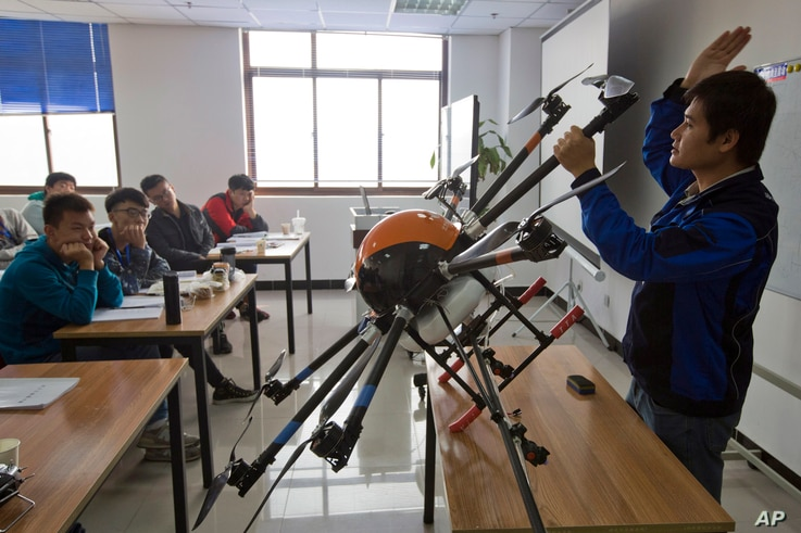 FILE - An instructor explains the operation of a drone to students at a school run by TT Aviation Technology in Beijing, Oct. 17, 2015. China has quickly emerged as a leading player in the international race for drone manufacturing.