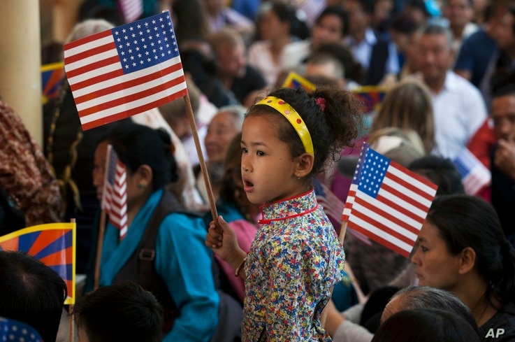 An exile Tibetan child holds the U.S. flag during a felicitation ceremony for a group of U.S. lawmakers at the Tsuglagkhang temple in Dharmsala, India, May 10, 2017.