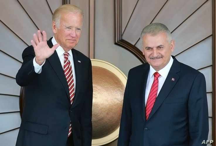 Turkish Prime Minister Binali Yildirim (R) as US Vice President Joe Biden waves as they pose for a photograph before their meeting at Cankaya Palace in Ankara, Aug. 24, 2016.