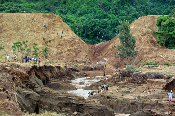 People gather in front of the broken banks of the Patel dam near Solai, in Kenya's Rift Valley, May 10, 2018.
