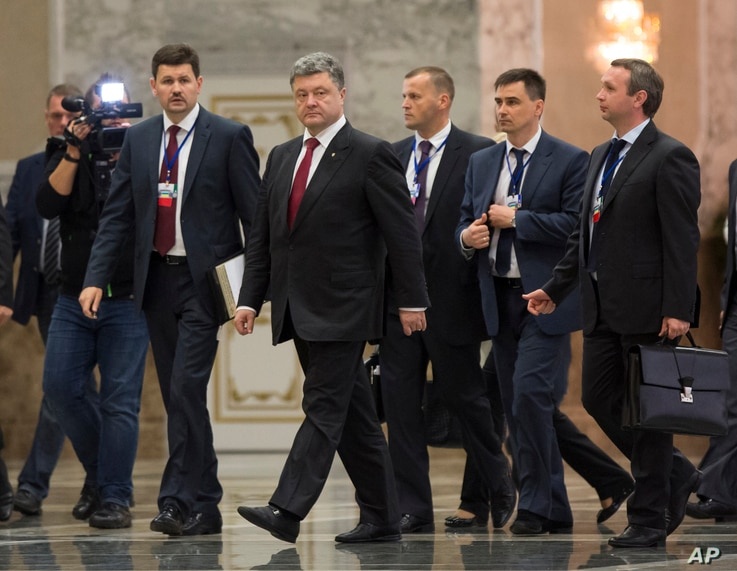 Ukrainian President Petro Poroshenko, center, leaves the hall after meeting with Russian President Vladimir Putin in Minsk, Belarus, Aug. 26, 2014.